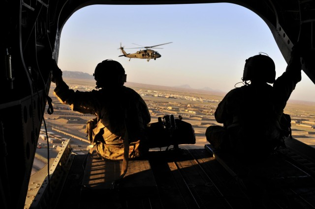 Sgt. 1st Class Edward Willis (left), quality control non-commissioned officer in charge, and Sgt. 1st Class Derek Walters, flight platoon sergeant, both with Company B, 3rd Battalion, 25th Aviation Regiment, 25th Combat Aviation Brigade, keep watch out the back of a CH-47F Chinook helicopter as it takes off during the early morning hours for an aircraft recovery mission with a UH-60 Black Hawk helicopter on Kandahar Airfield, Afghanistan, June 3.