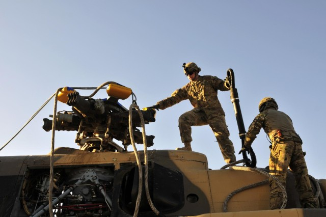 Chief Warrant Officer 2 Jorge Parra, downed aircraft recovery team officer in charge, Company B, 209th, 25th Combat Aviation Brigade, and Sgt. Colin Gragg, Headquarters and Headquarters Company, 3rd Battalion, 25th Aviation Regiment, 25th CAB position themselves on the top of an Mi-17 helicopter for sling load from a CH-47F Chinook helicopter during an aircraft recovery mission in Afghanistan, June 3.
