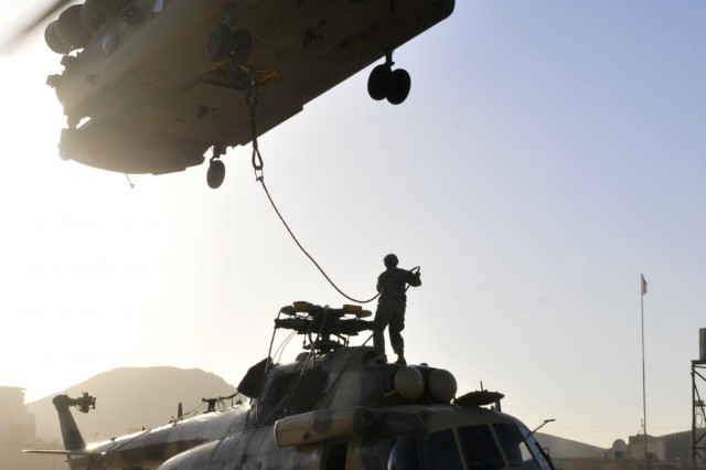 Sgt. Colin Gragg, Headquarters and Headquarters Company, 3rd Battalion, 25th Aviation Regiment, 25th Combat Aviation Brigade straightens out the sling load cables on an Mi-17 helicopter attached to a CH-47F Chinook helicopter from Company B, 3-25 AVN, 25th CAB, during an aircraft recovery mission in Afghanistan, June 3.
