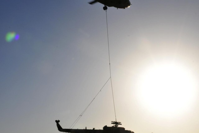 A CH-47F Chinook helicopter from Company B, 3rd Battalion, 25th Aviation Regiment, 25th Combat Aviation Brigade, takes off with an Mi-17 helicopter sling loaded on its way back to Kandahar Airfield, Afghanistan, during an aircraft recovery mission on June 3.
