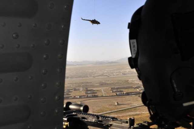 A CH-47F Chinook helicopter from Company B, 3rd Battalion, 25th Aviation Regiment, 25th Combat Aviation Brigade, flies steadily over the Afghanistan countryside with an Mi-17 helicopter sling loaded on its way back to Kandahar Airfield, Afghanistan, during an aircraft recovery mission on June 3.