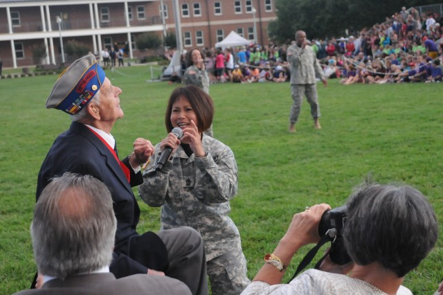 """A World War Two veteran jumps out of his chair and joins a member of the U.S. Army Band 'Downrange' during the U.S. Army Military District of Washington's Twilight Tattoo, performed by Soldiers from the 3rd U.S. Infantry Regiment (The Old Guard) and The U.S. Army Band """"Pershing's Own"""" at Joint Base Myer-Henderson Hall's Summerall Field, in Arlington Va., June 6, 2012.  Under Secretary of the Army Joseph W. Westphal hosted the show and invited a number of World War II veterans to view the performance as a salute to their service on the 68th anniversary of D-Day, the Allied invasion of France, June 6, 1944."""