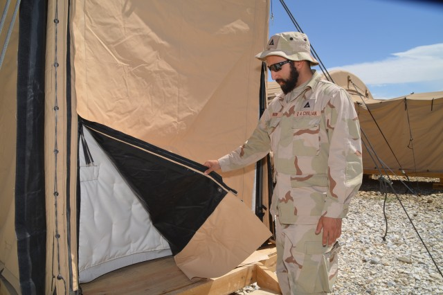 Gregory S. Dogum, RFAST-C power and energy expert, shows the insulated liner in one of the energy efficient tents at the energy efficient base camp housing Soldiers from Task Force Muleskinner.