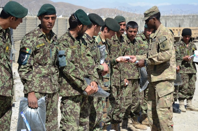 Afghan National Army soldiers receive care packages from Pfc. Curtis K. Blount, chaplain's assistant, Headquarters and Headquarters Company, 7th Engineer Battalion, at Camp Miawon, Logar Province, Afghanistan.