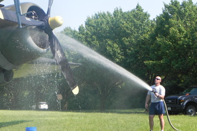 Air Force Master Sgt. Josef Hanson, a tactical air control party member with the 19th Air Support Operations Squadron, hoses off the engine of a Douglas C-47 Skytrain on display at Fort Campbell, Ky., June 1. The Skytrain is one of two aircraft on display that are currently undergoing restoration.