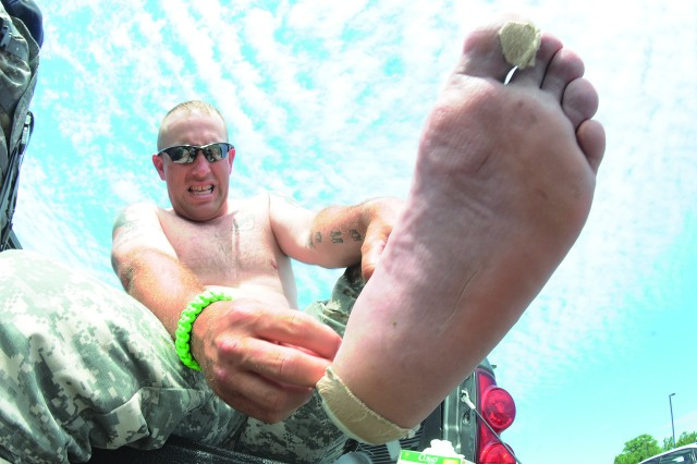 Sgt. 1st Class Patrick Kelly painstakingly removes a bandage from the heel of his foot during the 85-mile break of his 100-mile road march for cancer effort at Fort Lee, Va., June 4, 2012. Kelly, a cancer survivor, along with a battle buddy, Sgt. William Strickland, completed the march later in the evening.  They marched 25 miles a day for four consecutive days to raise money for cancer research.