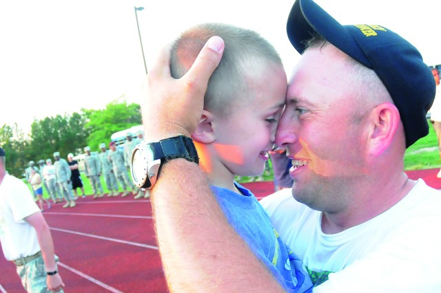 Sgt. 1st Class Patrick Kelly shares an affectionate moment with his son at the  after completing a 100-mile road march June 4, 2012, at Fort Lee, Va.