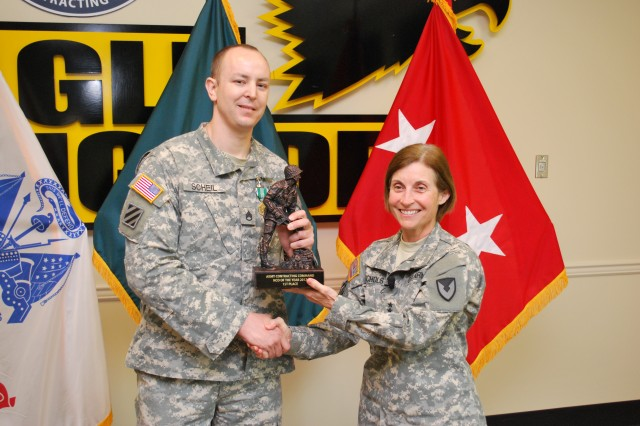 The 2012 Army Contracting Command Noncommissioned officer of the year, Staff Sgt. Jeremiah Scheil, 413th Contracting Support Brigade, Fort Shafter, Hawaii, receives his first place trophy from Maj. Gen. Camille Nichols, ACC commanding general at the June 8 ceremony at Redstone Arsenal, Ala.