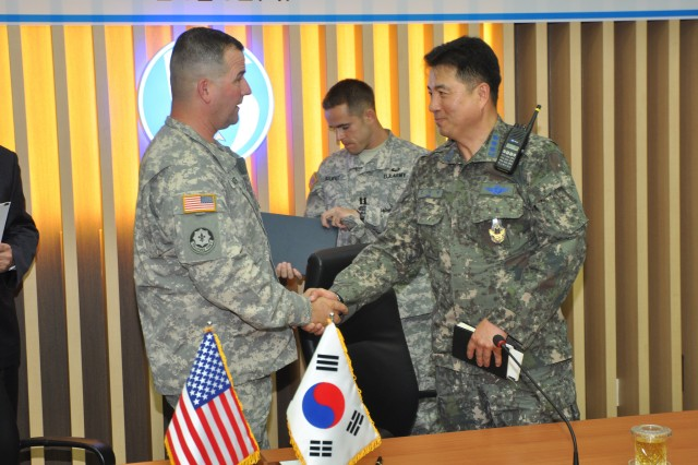 Col. William P. Huber, garrison commander for U.S. Army Garrison Yongsan, and Col. Kim, Ik-Hyun, support group commander for 15th Composite Wing, shake hands after signing an international Memorandum of Agreement between USAG Yongsan and the 15th CW at Seoul Air Base, June 5. (U.S. Army photo by Pfc. Lee Hyokang)