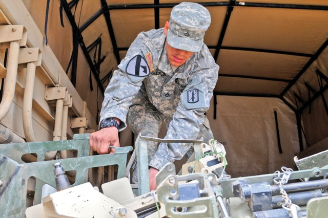 Pfc. Yancarlo Figueroa, 2nd Battalion, 18th Infantry Regiment, M249 machine gunner, loads equipment being inspected and signed over to Task Force Harvest in Baumholder, Germany.
