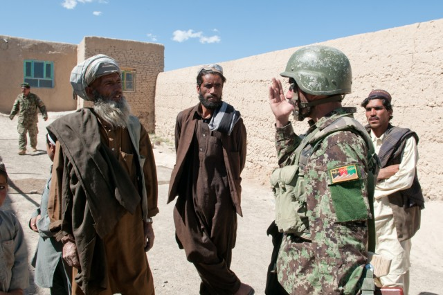 First Lt. Lashka Khan, an Afghan National Army officer, explains to villagers gathered outside a mosque for prayer why they should support the Afghan government and not the Taliban during a clearing operation of their village June 2, 2012, Ghazni Province, Afghanistan.  The officer found the villagers to be very receptive to his message.