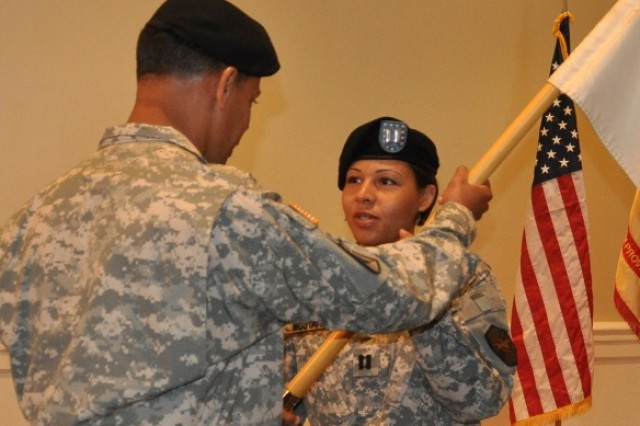 From left, Col. Orlando Ortiz, APG Garrison and deputy installation commander, passes the Garrison colors to Capt. Maritzabel Mustafaa, incoming commander, Headquarters and Headquarters Garrison, during the unit's Change of Command ceremony at Top of the Bay June 1.