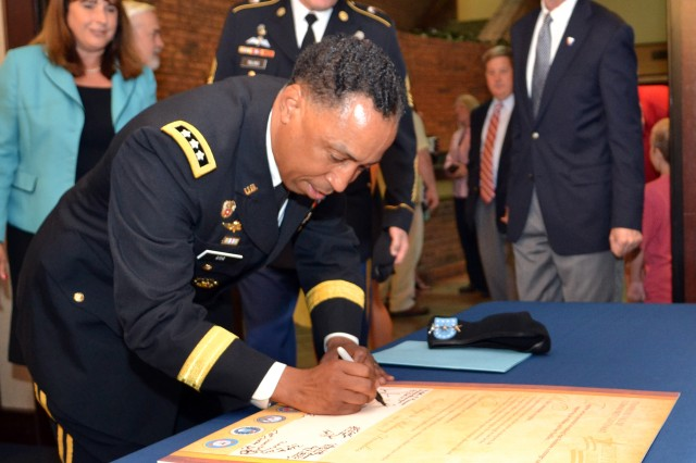 Lt. Gen. (P) Dennis Via, Army Materiel Command Deputy Commander signs a proclamation during Armed Forces Celebration Week.