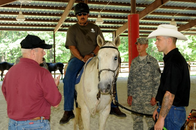Retired Command Sgt. Maj. Larry Pence, co-founder of Caisson Platoon Equine Assisted Program, gives a Therapeutic Riding Program lesson to Adam Porras, a Soldier in the Wounded Warrior Program, May 31, 2012, at the Caisson barn and stable on Fort Belvoir, Va. During these once a week lessons, Wounded Warriors learn different riding maneuvers on a horse is they choose to ride.