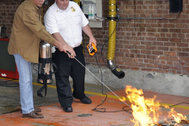 Even the Arsenal's Fire Chief, John Whipple, right, gets into the training as he coaches Patrick Mulligan in how to properly extinguish a small fire.