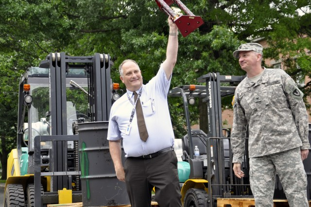 Arsenal Operations Director Tom Pond raises the trophy his team just won for the forklift rodeo competition, while Arsenal Commander Col. Mark F. Migaleddi looks on.