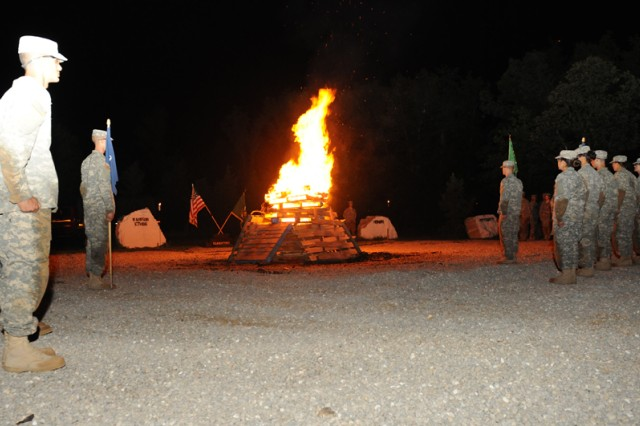 Soldiers from Company B, 795th Military Police Battalion, stand in formation around a bonfire during the unit's Value Tag Ceremony. For One Station Unit Training, the evening represented the culmination of Basic Combat Training.