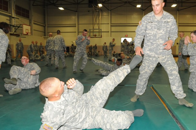 Pfc. Daniel West, on ground, and Pvt. Tyson Sutten, both Company C, 701st Military Police Battalion, practice unarmed self-defense moves during interment resettlement specialist Advanced Individual Training, June 12, 2012.