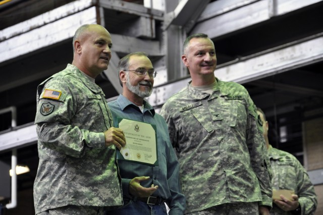From left, Maj. Gen. Kurt J. Stein presents a certificate of retirement to Dennis Downs in September 2011 with Arsenal Commander Col. Mark F. Migaleddi.