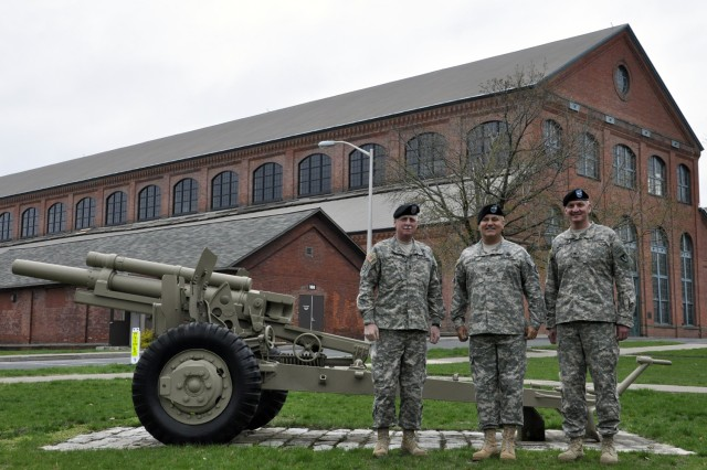 From left, TACOM LCMC Command Sgt. Maj. Clinton G. Hall, TACOM LCMC Commander Maj. Gen. Kurt J. Stein, and Watervliet Arsenal Commander Col. Mark F. Migaleddi take a break from an April 2011 tour to pose in front of the Arsenal's Historic Big Gun Shop.