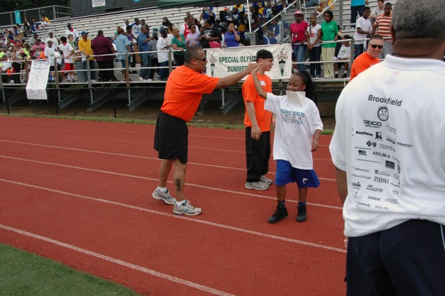 First Army Division East's Staff Sgt. Oscar Rodriguez high fives an athlete after the 25 meter dash during the Washington D.C. 2012 Summer Special Olympics.