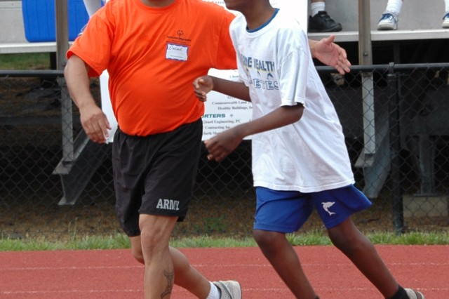 First Army Division East's Staff Sgt. Oscar Rodriguez encourages an athlete during the Washington D.C. 2012 Summer Special Olympics.