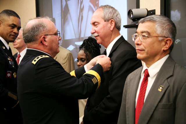 Lt. Gen. Richard P. Formica, commanding general, U.S. Army Space and Missile Defense Command/Army Forces Strategic Command, pins a new civilian lapel pin on Norven Goddard, director, Future Warfare Center Innovative Ventures Office, during the 237th Army Birthday celebration at the command's Redstone Arsenal headquarters June 12. Command Sgt. Maj. Larry S. Turner assisted Formica, and Dr. Steve Pierce, director, FWC Decision Support Directorate, awaits his turn.