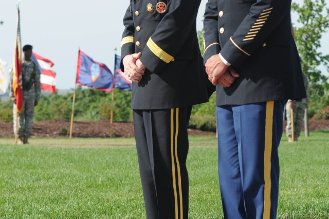 Fort Riley Senior Command Team Brig. Gen. Donald MacWillie and Command Sgt. Maj. Miguel Rivera pause for a moment of silence in front of Victory Park's newest memorial stones during the Victory Park Ceremony June 13 on Fort Riley. Stones etched with the names of 43 Soldiers who have died in Iraq or Afghanistan during the past year were unveiled during the ceremony. The central walkway in Victory Park is now lined with 498 stones bearing the names of Big Red One Soldiers who have died during recent operations in Iraq and Afghanistan.