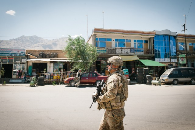 "Staff Sgt. Francisco Ballou, platoon sergeant of the 1st Infantry Division's ""Mercenary"" security platoon, walks down a highway in eastern Afghanistan's Parwan Province, June 11."