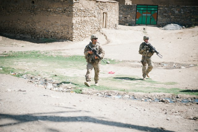 Staff Sgt. Francisco Ballou, left, and Spc. Glen Abbot patrol a road in eastern Afghanistan's Parwan Province, June 11. Assigned to the 1st Infantry Division's headquarters battalion, these Soldiers are charged with escorting military and government officials on governance and development missions in the province.