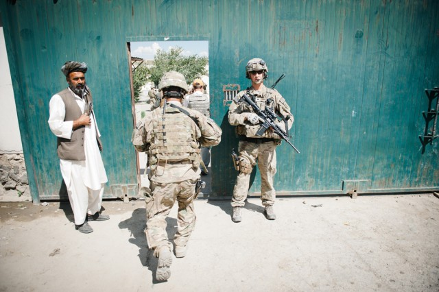 Spc. Charles Cothren, 1st Infantry Division, stands guard as Soldiers return to an Afghan compound following a mission in Parwan Province, Afghanistan, June 11.