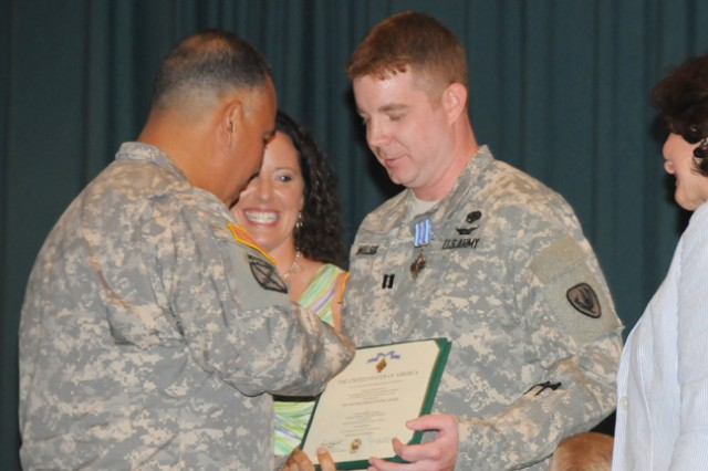 Maj. Gen. Anthony G. Crutchfield, U.S. Army Aviation Center of Excellence and Fort Rucker commanding general, presents the Distinguished Flying Cross to Capt. Andrew Wilson as his wife, Karen, watches June 8.
