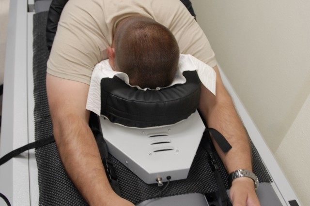 "Spc. Michael Overturf, 4th Combat Aviation Brigade, uses the Vertebral Axial Decompression table "" for nonsurgical lumbar decompression "" at the Center for Integrative Medicine on Fort Bliss. (Photo by Jennifer Clampet)"