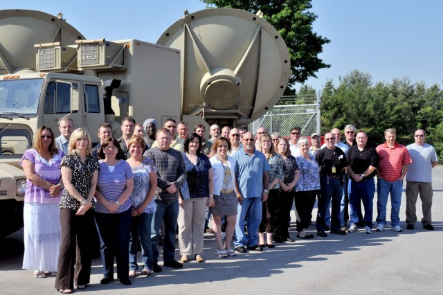 Staff members from the Fort Drum Network Enterprise Center, which was named the 2012 Best Large NEC in 7th Signal Command, pose for a photo in front of their Unit Hub Node assembled behind NEC headquarters. Called an IAAD, or Installation as a Docking Station, the state-of-the-art equipment is configured in a way that Soldiers would experience it in a tactical environment.