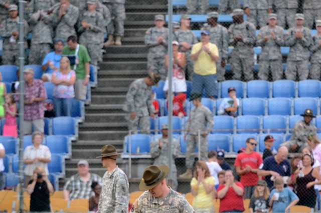 Gabe, the former military dog in the running for a national award, and his former handler and current owner, Sgt. 1st Class Chuck Schuck, Drill Sergeant School, take the field between innings.