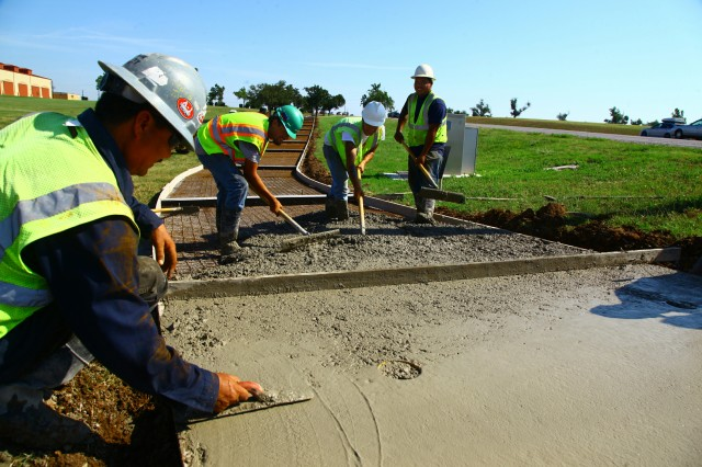 Workers from MS Concrete Construction of Lawton, smooth out a sidewalk June 8 near Hoskins Road at Fort Sill Boulevard here. It was one of three sidewalk projects under way at Fort Sill.