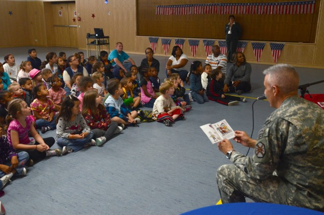 "Col. James Saenz, U.S. Army Garrison Grafenwoehr commander, reads the book ""Happy Birthday, U.S. Army!"" to a group of children at the Netzaberg Elementary School on the Army's birthday, June 14."