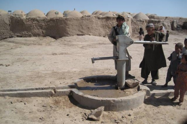 Local children and youth in Afghanistan pump water from the well, for which 1/64 Armor Regt., 2BCT, 3rd ID has provided assistance.