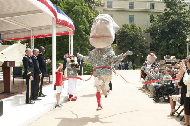 "Crossing the finish line during the ""Running Presidents"" race is George Washington, one of the mascots for the Washington Nationals baseball team.  Cheering are Gen. Martin Dempsey, 18th Chairman of the Joint Chiefs of Staff and the Army's 37th Chief of Staff; Secretary of the Army John McHugh; Vice Chief of Staff of the Army Gen. Lloyd J. Austin III, and the Nationals' other mascot ""Screech.""  The Pentagon celebration of the Army's 237th birthday was held in the center courtyard June 14, 2012. (Army photo by Spc. John G. Martinez)"