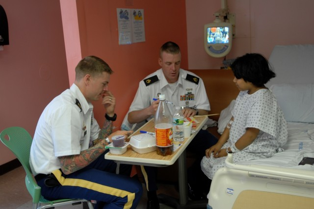 Two Soldiers from the 10th Mountain Division sit with an ill child and draw to brighten up the child's day at a hospital in Queens, N.Y., June 13.