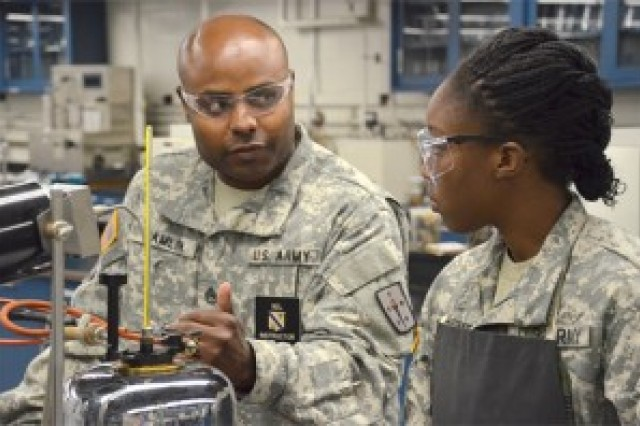Staff Sgt. Ricardo Hamlin, PWD Laboratory Training Division team chief, discusses fuel testing with Advanced Individual Training student Pfc. Tationna Rockwood during a laboratory session recently. Hamlin earned the Outstanding Quality Manager award from the National Petroleum Management Association May 30.