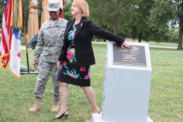 After unveiling a marker Thursday, near the dogwood tree planted in memory of Brig. Gen. Terence J. Hildner, former commanding general of the 13th Sustainment Command (Expeditionary), Fort Hood, Texas, Brig. Gen. Gwen Bingham, Quartermaster General and QM School commandant, escorts Cindy Hildner, Hildner's widow, back to her seat. The tree and plaque are located near the 1st Logistics Command War Memorial. From July 2007 to 2010, Hildner served at Fort Lee, where he commanded the 23rd QM Brigade, QM School, and then served as the Combined Arms support Command G3/director, Training and Doctrine. Hildner died Feb. 3 in Kabul, Afghanistan, of natural causes.