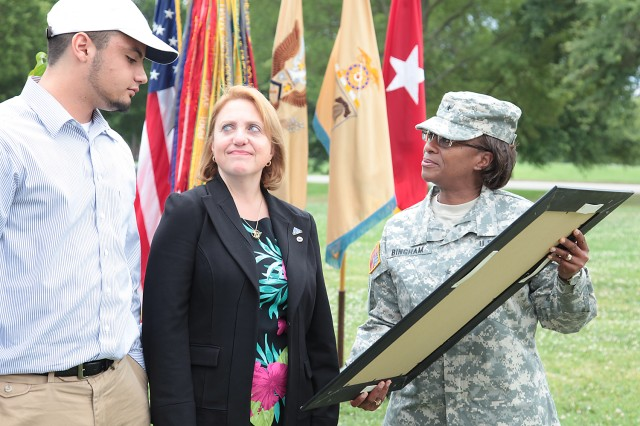 Brig. Gen. Gwen Bingham, Quartermaster General and QM School commandant, presents Cindy Hildner and Jonathan Hildner with a plaque displaying the dogwood tree that was planted in honor of Jonathan's father and Cindy's husband, Brig. Gen. Terence J. Hildner, during a ceremony at Fort Lee, Va., Thursday. The ceremony honored the memory of the former 23rd QM Brigade commander, whose final command was of the 13th Sustainment Command (Expeditionary), Fort Hood, Texas. Hildner died Feb. 3 in Kabul, Afghanistan, of natural causes.