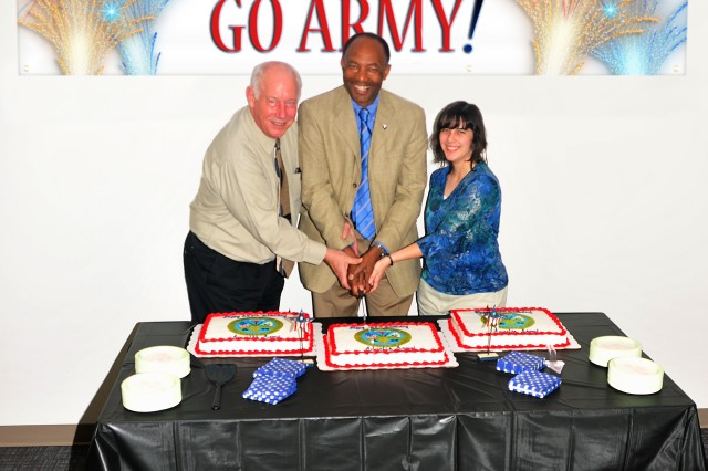 Robert Moore (center), deputy to the commanding general of the U.S. Army Security Assistance Command, is joined by Gary Burkavich and Kandi Russell for the Army birthday cake cutting June 14. Burkavich and Russell represent the oldest veteran and youngest civilian at USASAC.