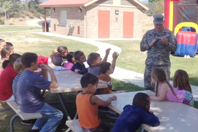 Col. James Suriano, Fort Hunter Liggett garrison commander, reads the 237th Army Birthday story to students from the Children, Youth and Student Services program on post, wrapping up this year's The U.S. Army birthday celebration. (U.S. Army photo by Command Sgt. Maj. Kevin Newman)