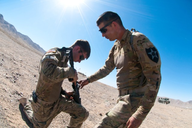 Spc. Adam Taylor (left) a native of Sumner, Wash. and an infantryman, gets his weapon inspected by Sgt. 1st Class Donald Register, a native of Wilmington, N.C. and an infantry platoon sergeant June 12 at Fort Irwin, Calif. Both Soldiers are assigned to 1st Battalion, 38th Infantry Regiment, 4th Stryker Brigade Combat Team, 2nd Infantry Division, and are currently training at the National Training Center preparing for an upcoming deployment later this year.