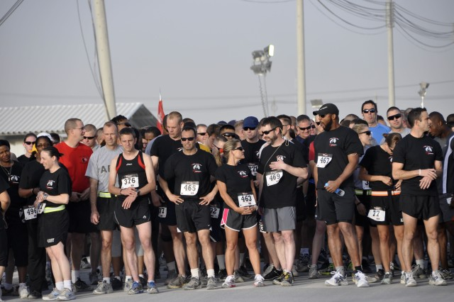 """Runners from all over Kandahar Airfield await the start of the Engineer Day 5-kilometer run. Runner number 376, Royal Air Force Sgt. Paul Vernon (left front), was the first place finisher. The first place female runner was a U.S. Army runner""""2nd Lt. Jennifer Han who works at the KAF medical center."""