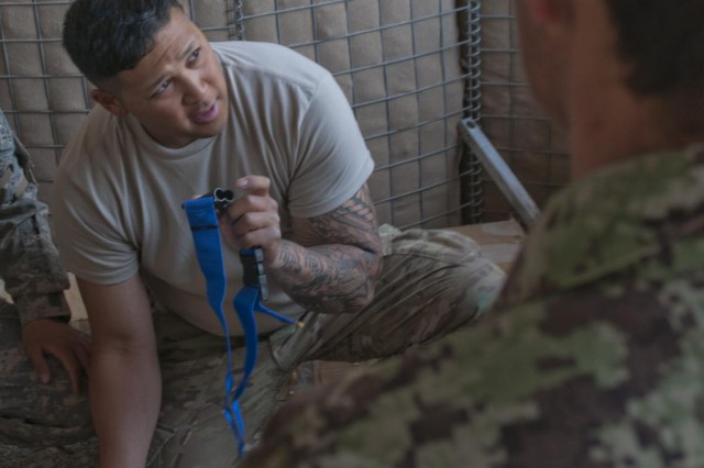 Pfc. Curtis Sua Fo-a, who serves as a medic with the Headquarters and Headquarters Battery, 2nd Battalion, 17th Field Artillery Regiment, 2nd Stryker Brigade Combat Team, 2nd Infantry Division, shows medics with the Afghan National Army, Medical Platoon, 1-205th Corps, the steps he uses when using a leg splint during medical partnership training at Forward Operating Base Frontenac, Afghanistan, June 11-14, 2012.