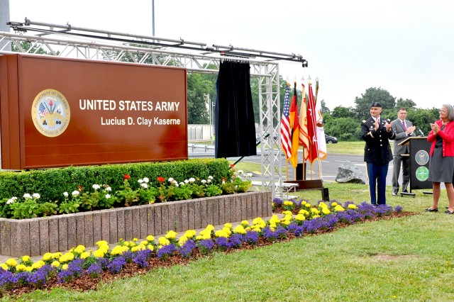 Col. David Carstens, U.S. Army Garrison Wiesbaden commander, is joined by Cathleen Ketcham and Lucius D. Clay III, Gen. Lucius D. Clay's grandchildren, in unveiling the new name of Wiesbaden Army Airfield -- Clay Kaserne, in Germany.