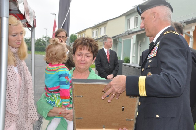 Lt. Gen. Mark Hertling, U.S. Army Europe commander, presents Angelika Broer with plaque during the opening of Newman Village on Clay Kaserne. Broer's son, Dr. (Maj.) Thomas Broer was killed in Afghanistan in 2010. One of the new streets in Newman Village was named in his honor.